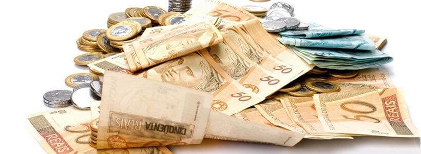 Muito dinheiro reunido como notas de cinquenta, cem, e moedas de um real, cinquenta centavos